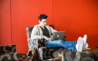 Student on laptop sitting in comfortable chair