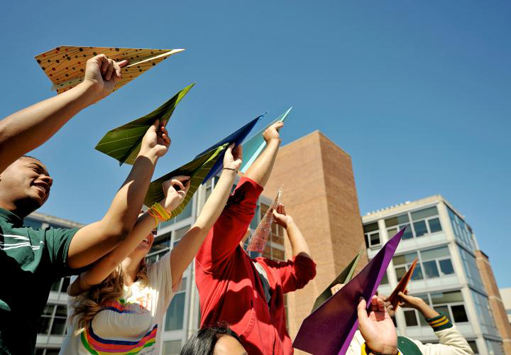 Students holding paper airplanes to the sky.